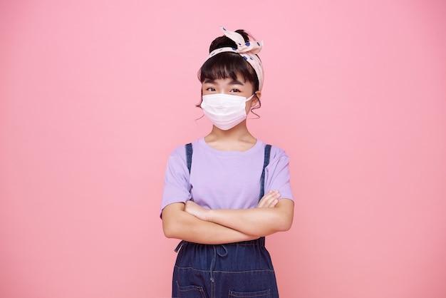 Asiatisches kleines mädchen, das maske trägt, um sie vor virus covid-19 zu schützen, isoliert auf rosa wand.