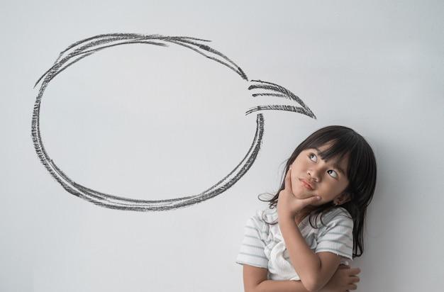 Asiatisches kleines mädchen, das mit leerer wolkenblase denkt