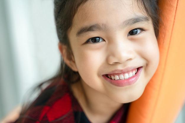 Asiatisches kleines mädchen, das mit perfektem lächeln und den weißen zähnen in der zahnpflege lächelt