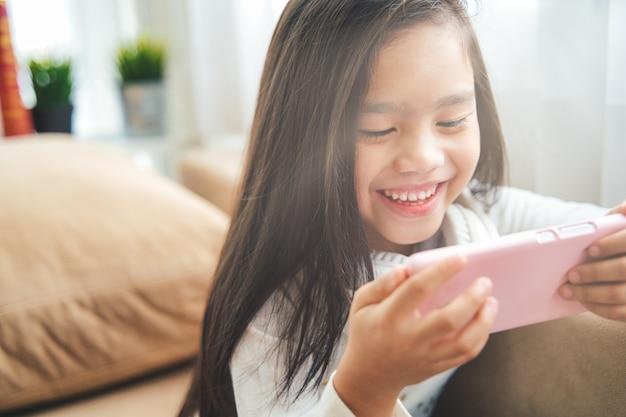 Asiatisches kleines mädchen, das mit smartphone spielt
