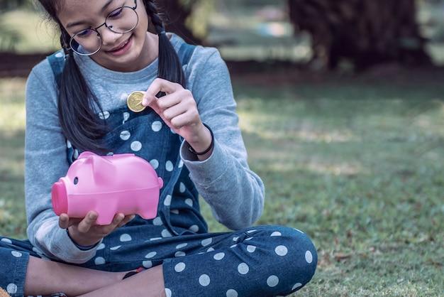 Asiatisches kleines mädchen, das münze in sparschwein im park steckt.