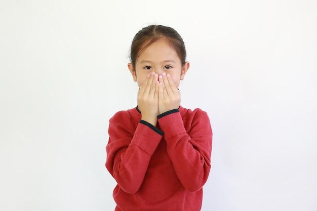 Asiatisches kleines mädchen, das mund durch hände mit schauender kamera bedeckt