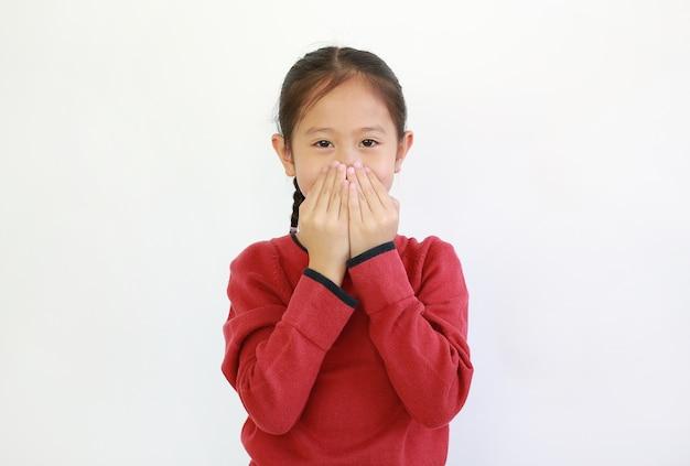 Asiatisches kleines mädchen, das mund mit händen auf weiß bedeckt