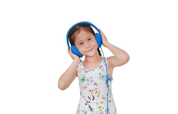 Asiatisches kleines mädchen, das musik durch kopfhörer auf weiß hört