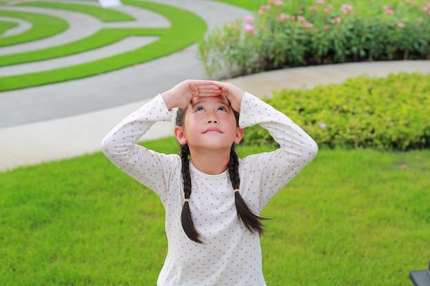 Asiatisches kleines mädchen, das oben mit den händen über dem kopf im garten schaut