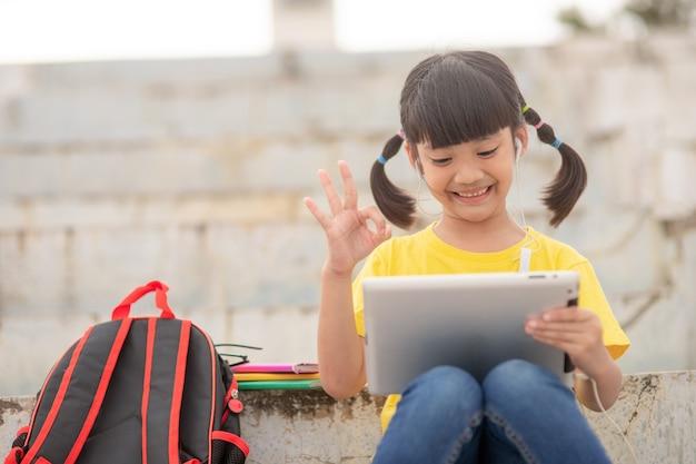 Asiatisches kleines mädchen, das online unterricht nimmt und glücklich ist