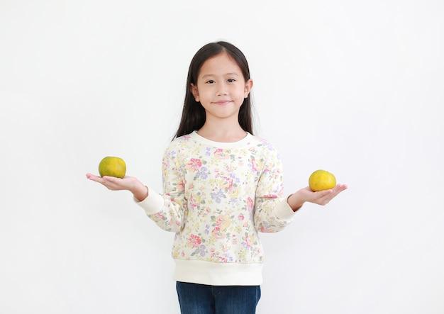 Asiatisches kleines mädchen, das orange frucht auf weiß hält