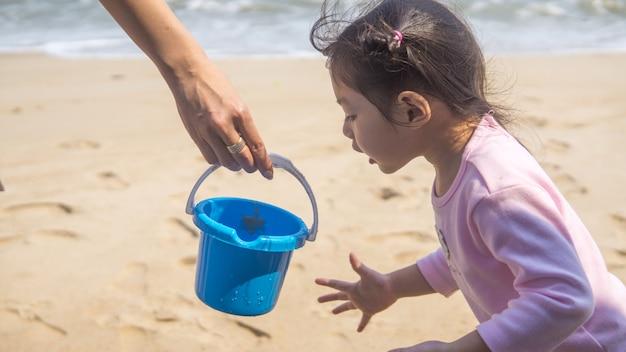 Asiatisches kleines mädchen, das sand am strand im freien plaiert.
