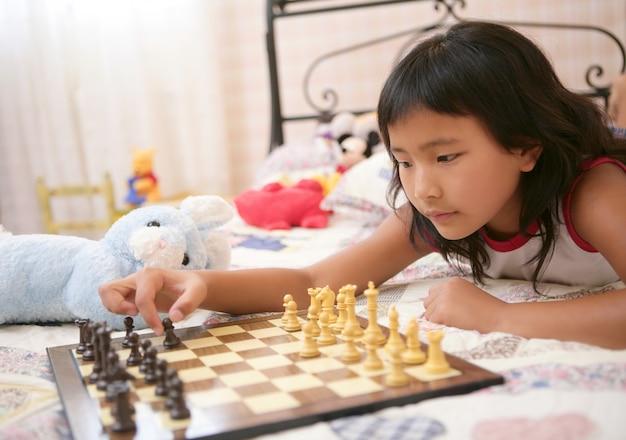 Asiatisches kleines mädchen, das schach mit teddybären spielt