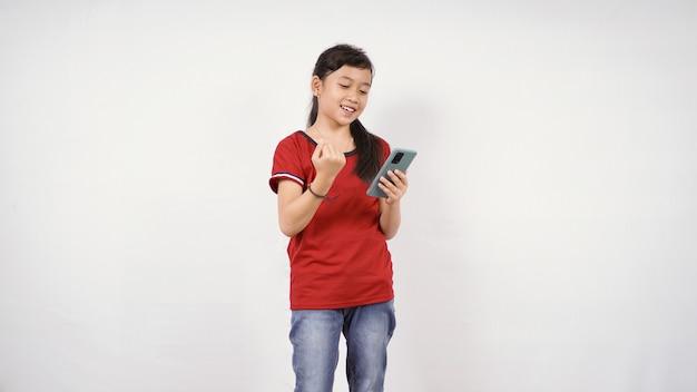 Asiatisches kleines mädchen, das sich mit ihrem smartphone-spiel erfolgreich fühlt, isoliert auf weißem hintergrund