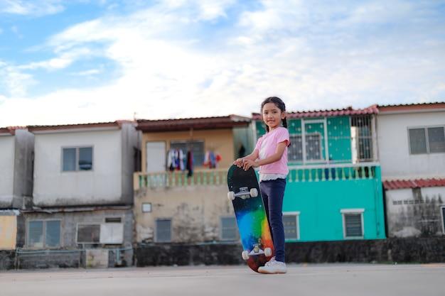 Asiatisches kleines mädchen, das skateboard und lächeln mit flacher schärfentiefe des ausgewählten fokus der glückstadt und des blauen himmels hält