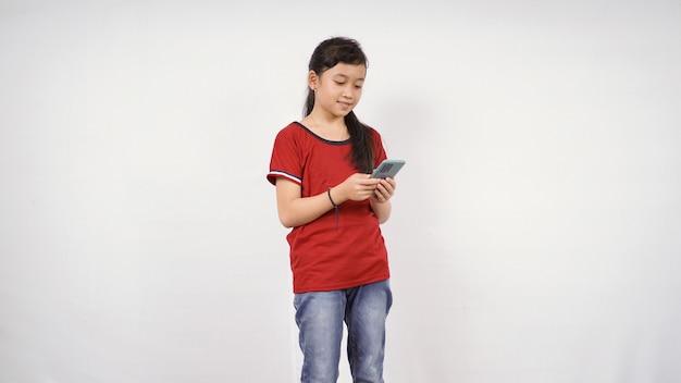 Asiatisches kleines mädchen, das smartphone isoliert auf weißem hintergrund spielt