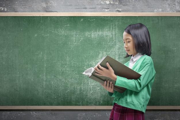 Asiatisches kleines mädchen, das steht und das buch im klassenzimmer liest