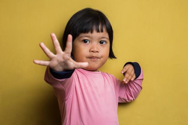 Asiatisches kleines mädchen, das stoppgeste mit ihrer hand macht