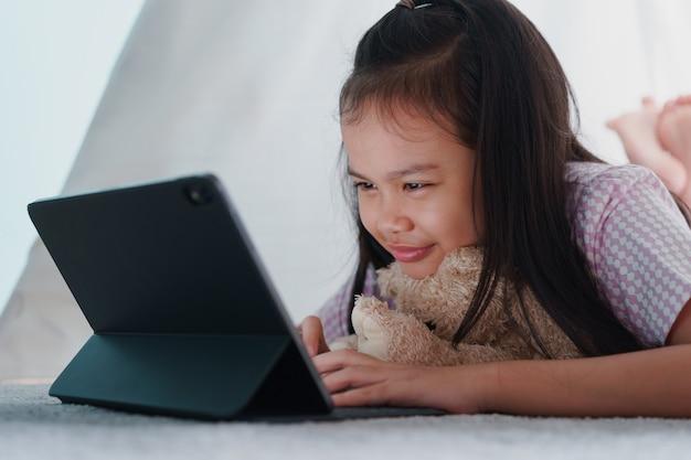 Asiatisches kleines mädchen, das tablette in einem zelt zu hause nacht verwendet