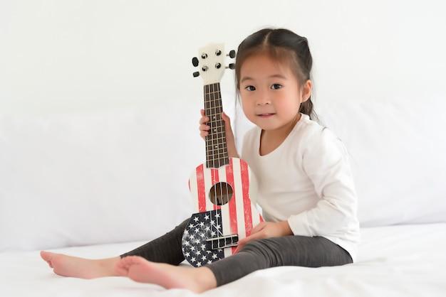 Asiatisches kleines mädchen, das ukulele im schlafzimmer spielt