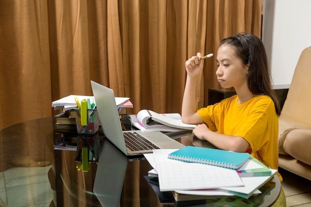 Asiatisches kleines mädchen, das zu hause ihre hausaufgaben mit laptop macht. online-bildung während der quarantäne
