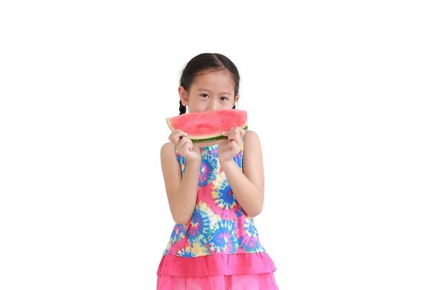 Asiatisches kleines mädchen des porträts, das wassermelone lokalisiert auf weißem hintergrund isst