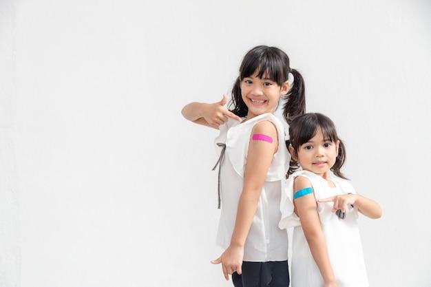 Asiatisches kleines mädchen fühlt sich gut, nachdem es einen impfstoff erhalten hat.