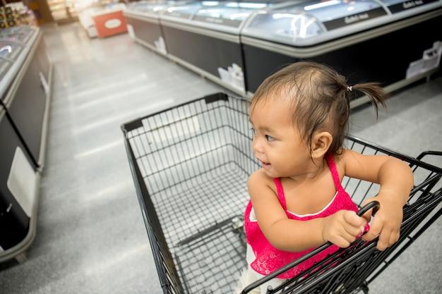 Asiatisches kleines mädchen im einkaufswagen