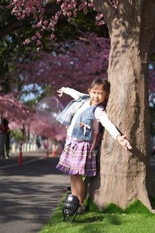 Asiatisches kleines mädchen im garten unter dem blüten-sakura-baum