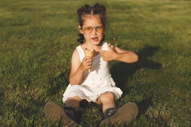 Asiatisches kleines mädchen im weißen kleid und in der sonnenbrille, die eis auf dem rasen im sommer essen