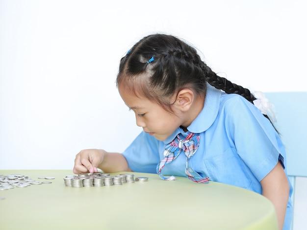 Asiatisches kleines mädchen in der schuluniform, die auf tisch mit stapel von münzen für das speichern sitzt. kind zählt geld. schulmädchen mit geld sparen für das zukünftige konzept.