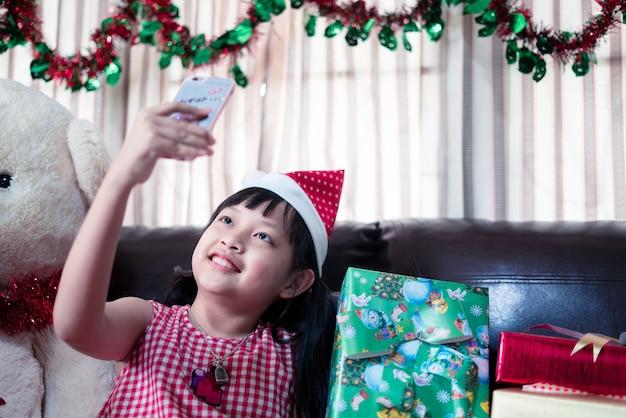 Asiatisches kleines mädchen in einer weihnachtsmann-weihnachtsmannmütze schaut auf ein smartphone für videoanruf