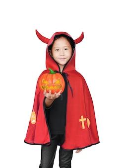 Asiatisches kleines mädchen kleidete im halloween-kostüm an, das in der hand magischen kürbis hält