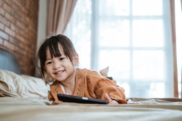 Asiatisches kleines mädchen lacht glücklich, wenn es in die kamera schaut und hält ein telefon