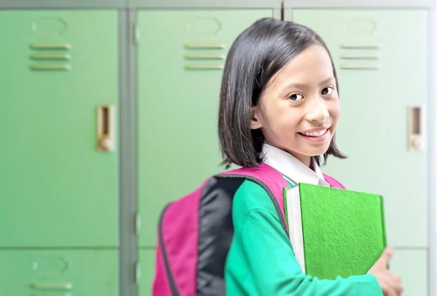 Asiatisches kleines mädchen mit buch und rucksack auf der schule. back to school-konzept