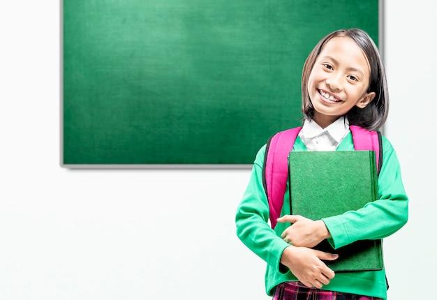 Asiatisches kleines mädchen mit buch und rucksack im klassenzimmer. back to school-konzept