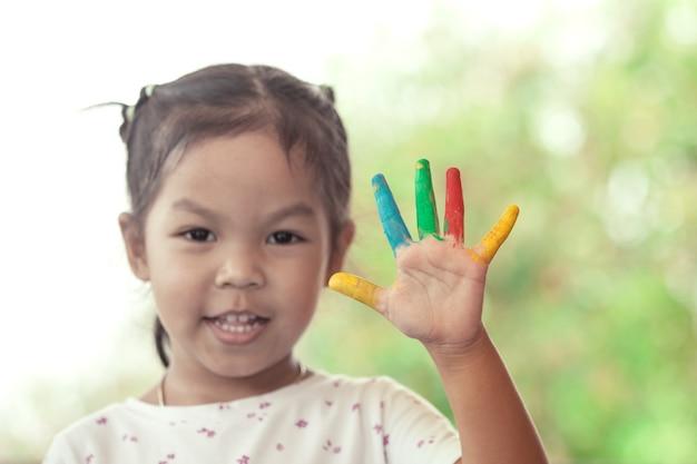 Asiatisches kleines mädchen mit den gemalten händen