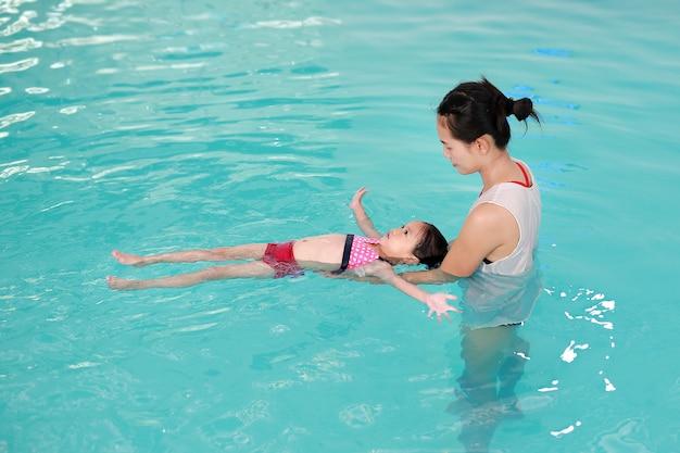 Asiatisches kleines mädchen mit der mutter, die am wasserpool schwimmt