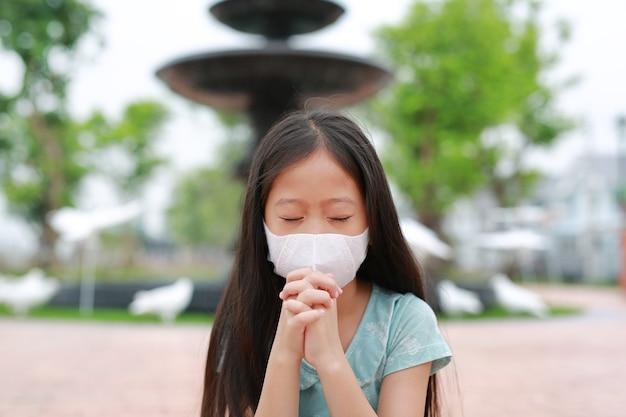 Asiatisches kleines mädchen mit gesichtsmaske und gebetsgeste, um covid-19 während des ausbruchs des coronavirus zu stoppen