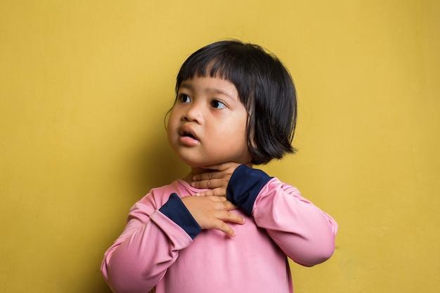 Asiatisches kleines mädchen mit halsschmerzen, die ihren hals berühren. halsschmerzen krank. kleines mädchen, das schmerzen im hals hat