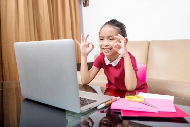 Asiatisches kleines mädchen mit laptop, das zu hause an der online-schulklasse teilnimmt. online-bildung während der quarantäne