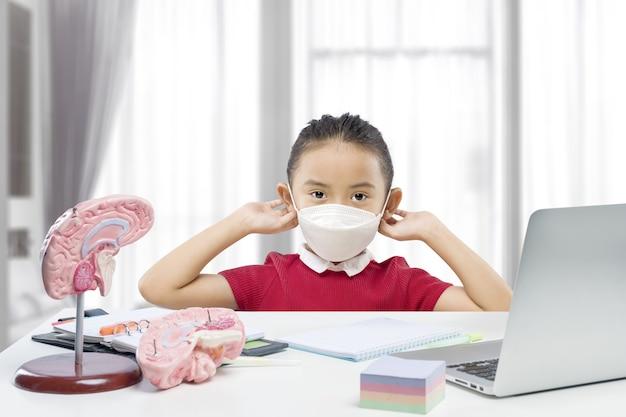 Asiatisches kleines mädchen mit maske und laptop, das zu hause an der online-schulklasse teilnimmt. online-bildung während der quarantäne