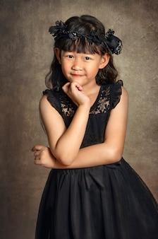 Asiatisches kleines mädchen mit schwarzem kleid