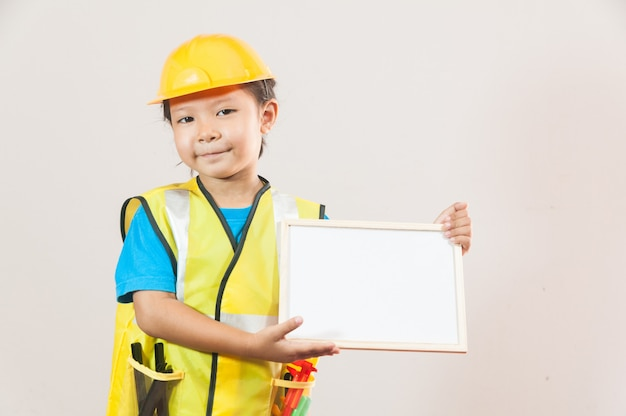 Asiatisches kleines mädchen oder kinder im blauen hemd und im gelben hardhat stehend und hält whiteboard in der hand