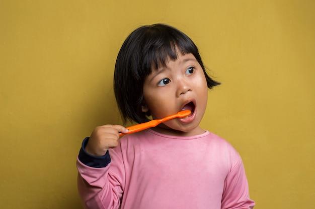 Asiatisches kleines mädchen putzen ihre zähne auf gelber wand