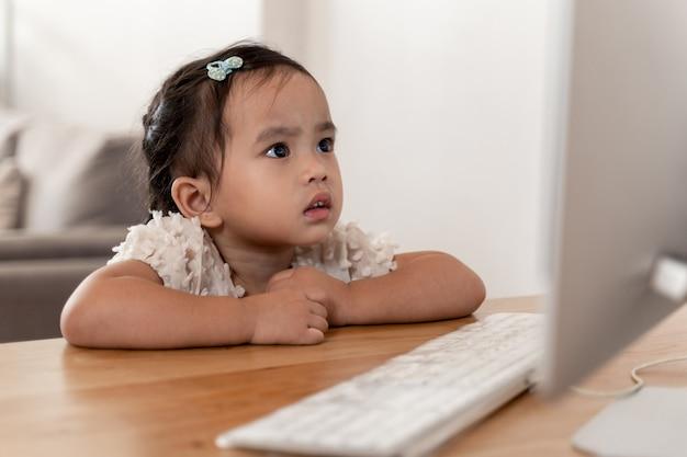 Asiatisches kleines mädchen saß auf einem computerbildschirm und konzentrierte sich auf spiele oder cartoons auf dem bildschirm.