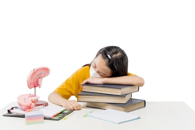 Asiatisches kleines mädchen schläft beim lernen von zu hause isoliert über weißem hintergrund ein. online-bildung während der quarantäne