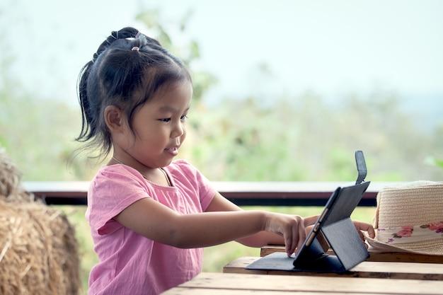 Asiatisches kleines mädchen spielt ipad tablette im weinlesefarbton