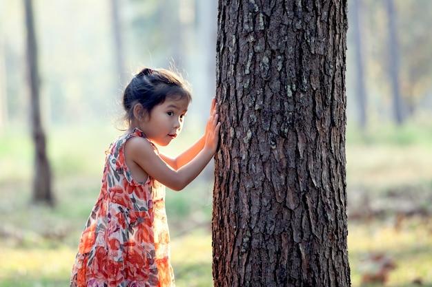Asiatisches kleines mädchen spielt verstecken im park