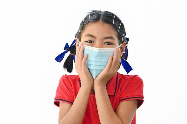 Asiatisches kleines mädchen trägt medizinische gesichtsmasken, um sich vor coronavirus zu schützen