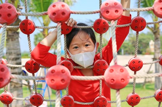 Asiatisches kleines mädchen tragen schutzmaske, die auf kletterseilnetz spielt