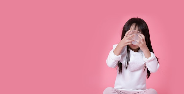 Asiatisches kleines mädchen trank die ganze milch von einer klaren schale mit einer schürze, die zum hemd mit copyspace gesunder ernährung angebracht wurde.