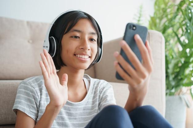 Asiatisches kleines mädchen videoanruf mit einem headset auf dem smartphone und winkend zur begrüßung beim sitzen im wohnzimmer