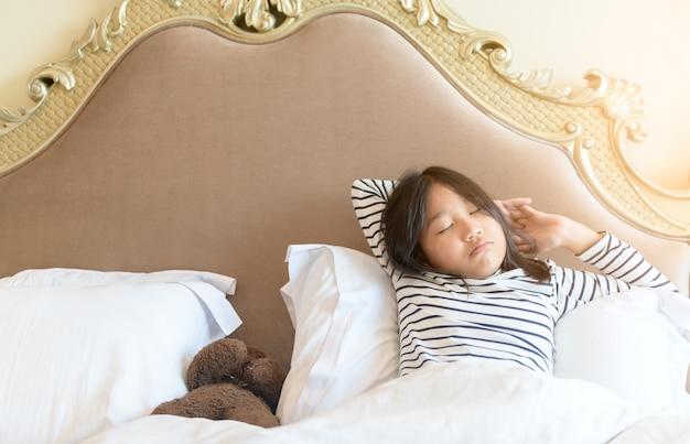 Asiatisches kleines mädchen wacht auf und streckt sich am morgen auf dem bett, gesundes konzept